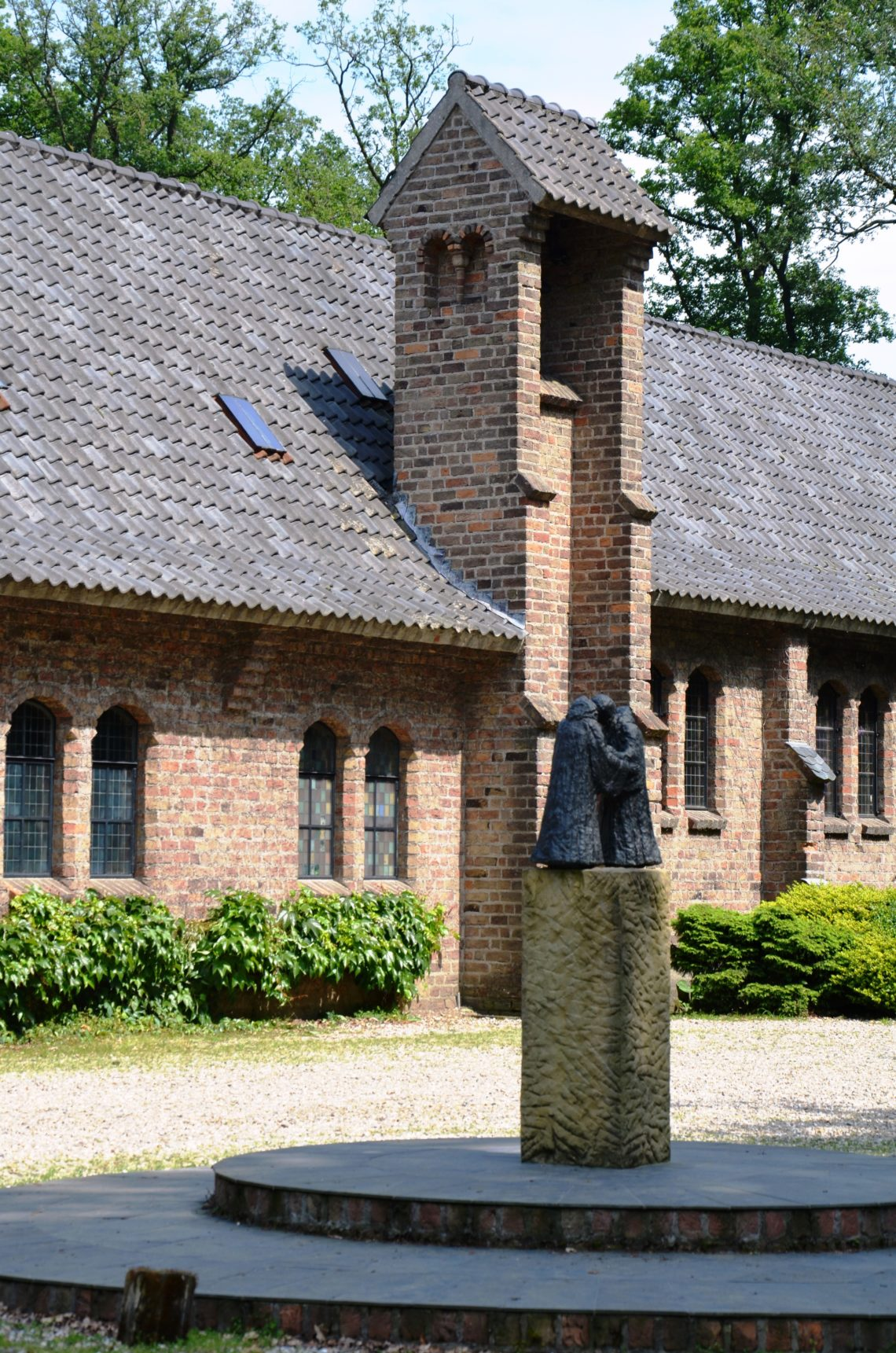To the right of the entance to the Willibrordus abbey, with a small statue of franciscan brothers on a pilar in front. Part of the abbey in the back with green bushes in front and tower bell in the middle.