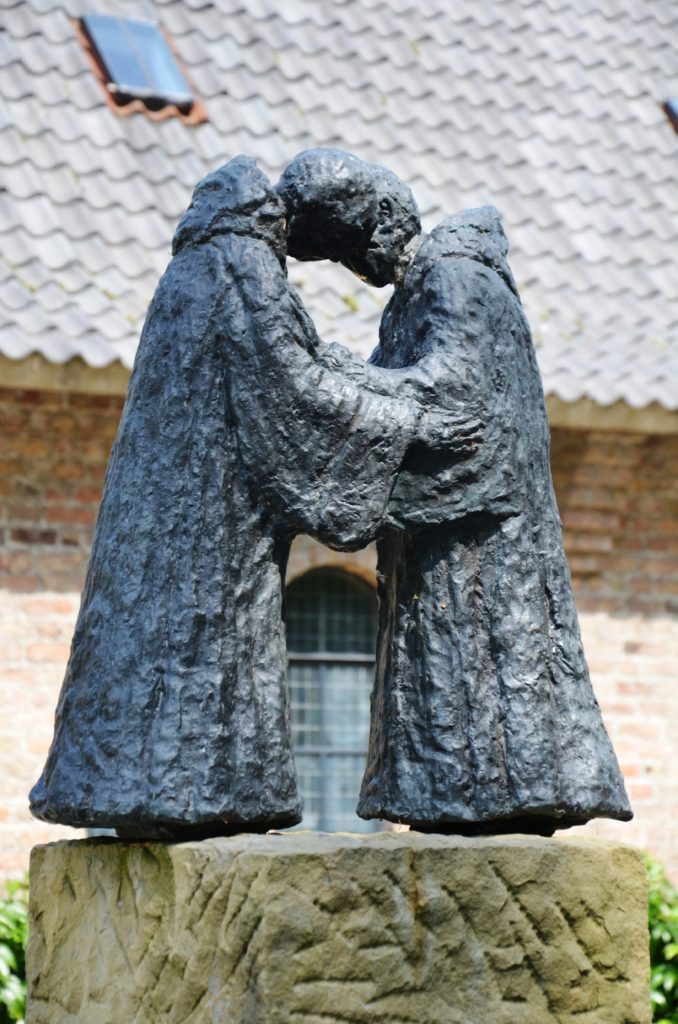 Statue of 2 Franciscan brothers they hold hands and bow to eachother