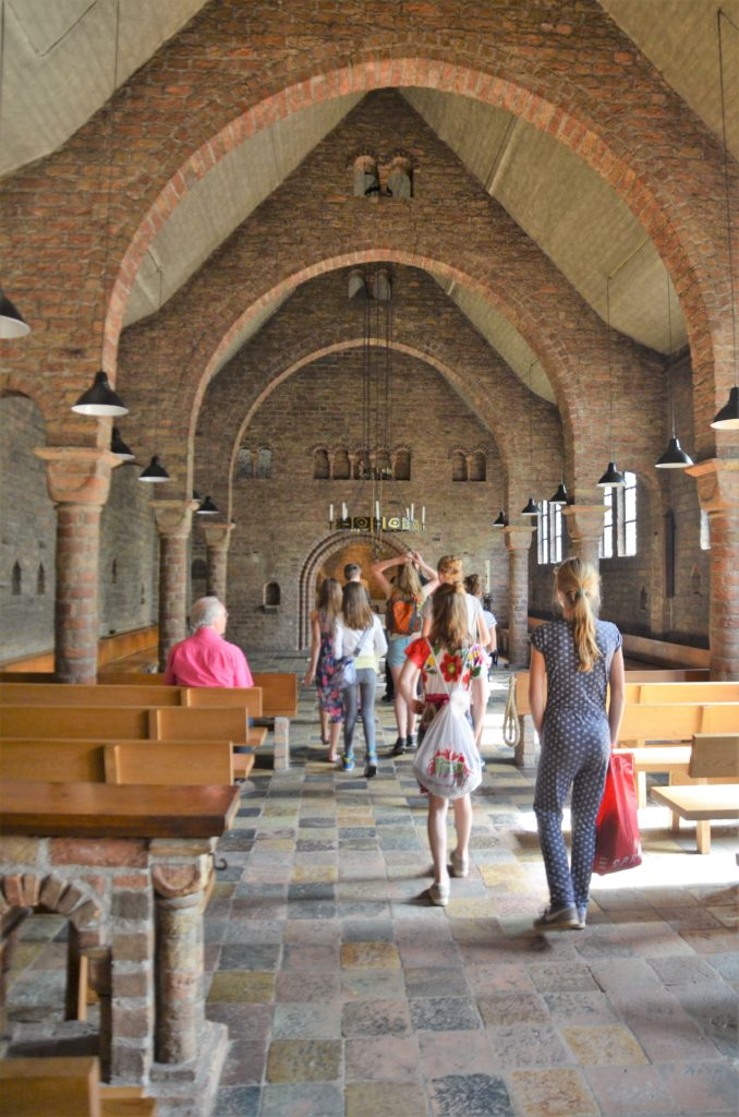 The chapel of the abbey, inside with youths walking in the middle and someone sitting in the banches to the left. On the left and right side are benches in the forefront of the picture, In the back is the altar and a large hanging candleholder. In the back are archways on the left and right side. You can visit teh chapel on a visit of the Willibrordus abbey