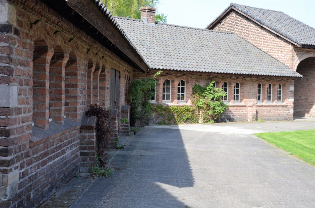 Part of the backside of the abbey. You see on the left and behind the abbey; roof and walls. There's green plants against the walls and a tree sticks out behind the building in the back.