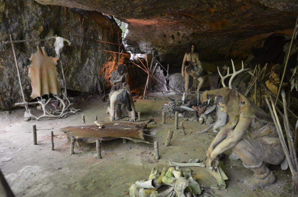A display with mannequins visualising how the cavemen would have lived in prehistoric times in the caves. They're working on hides and bones, making them into clothing and usefull items.