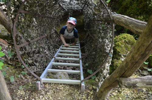 Yuri climbing up a ladder, surrounded with camouflage. Part of the adventure path for children.