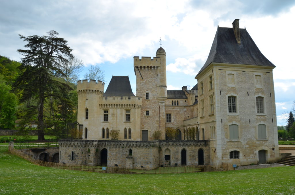 Chateau de Campagne seen from the front. Standing in a field of green grass. The castle is made from yellow stone.