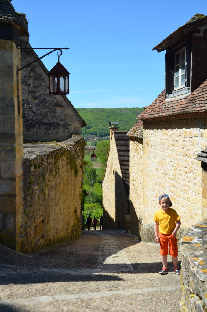 A cobblestone street in Beynac, with Yuri standing in the foreground. The street goes down and is steep and smaller towards the end. Buildings rise up on both sides. In the back you see the green country.