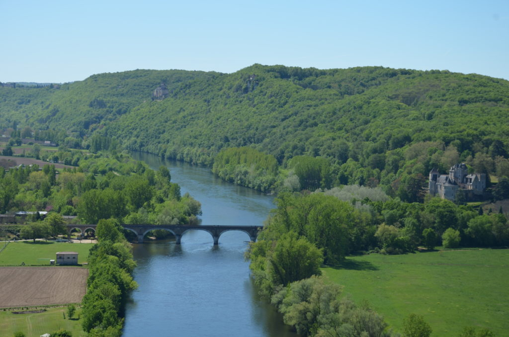The Dordogne river with green forest on both sides and a green grass field in the right front. In the middle a bridge spanning the Dordogne river.
