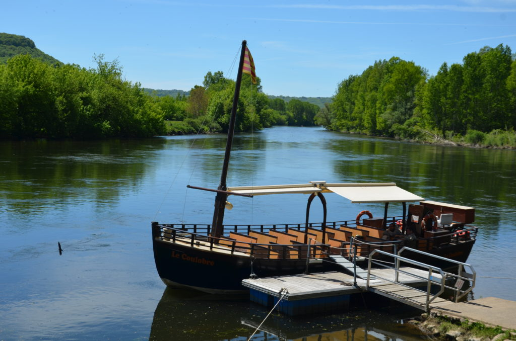 The river Dordogne with green bushes and trees on either side. In the front a dock with a gabarre moored on it. To visualise Dordogne with kids