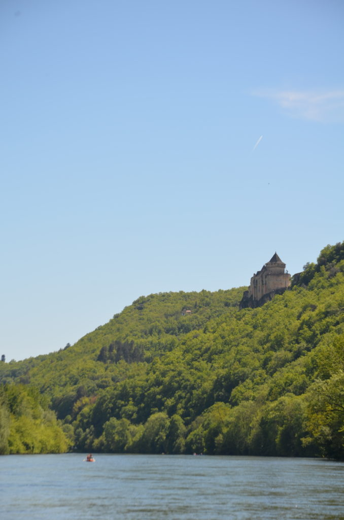 A third castle towers high above out of the green forest on a mountain. Blue sky above it and far down the Dordogne river.