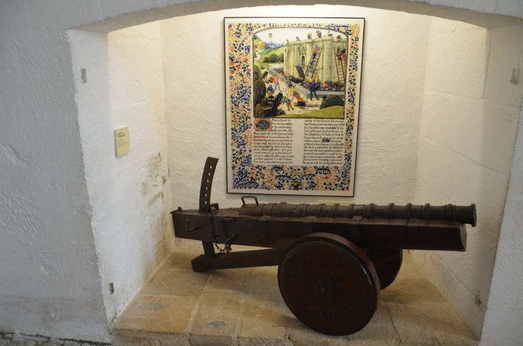 In the picture is a canon and behind it on the wall is an old medieval page from a book showing the way the canon was used in a siege