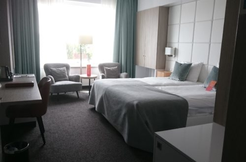 A hotelroom at Van der Valk Hotel Tiel, with a double bed, 2 chairs next to the window with a small table in between