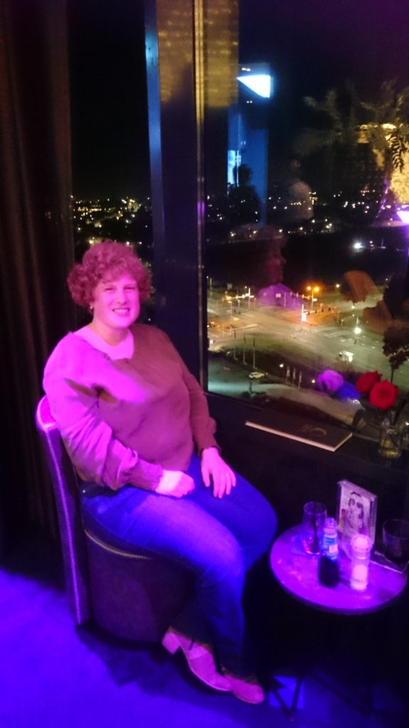 Cosette sitting in a chair in front of a window at night. It's at the skybar on top of the hotel. In front of her a small table with a drink.