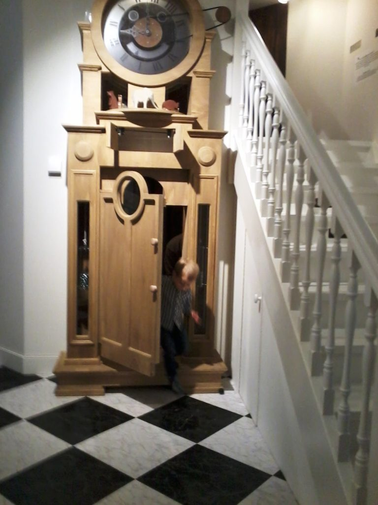 A large wooden clock, where Yuri is walking out through a door. On the right side is a white staircase.