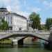 Stone bridges over canals. Tromostovje, triple bridge, underneath water, with a small boat on it. On the left a large white plastered building. On the right trees and above a blue sky with some white clouds. Afternoon in Ljubljana.