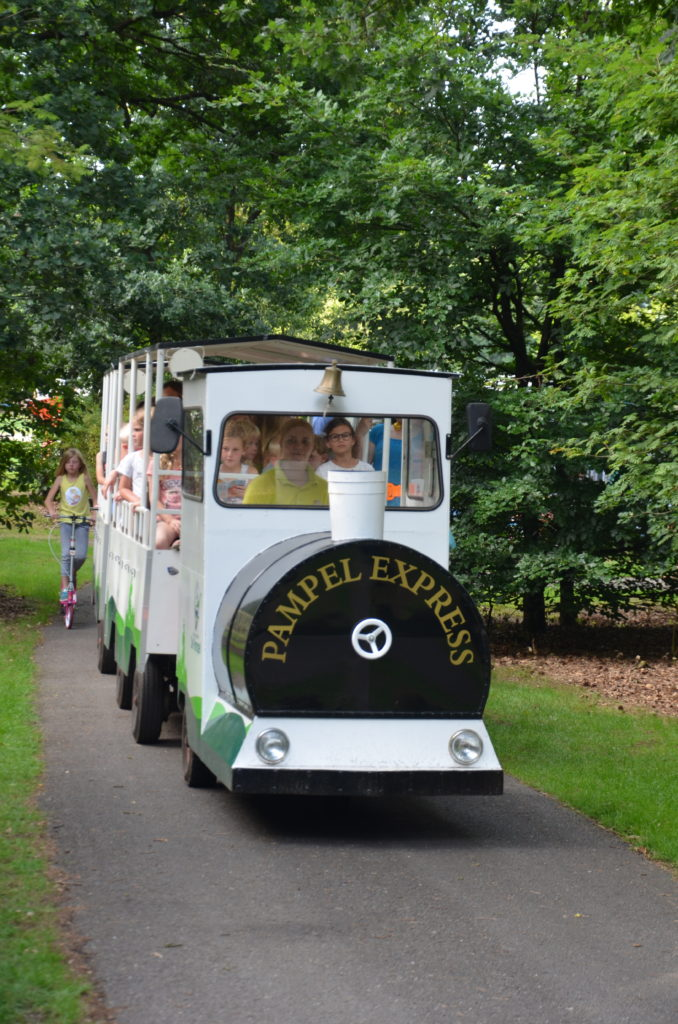 To show the train for children on the campsite. A small train on wheels for children. Pampel Express stands on the front. It's driving on the road inside the campsite. Campsites in The Netherlands.