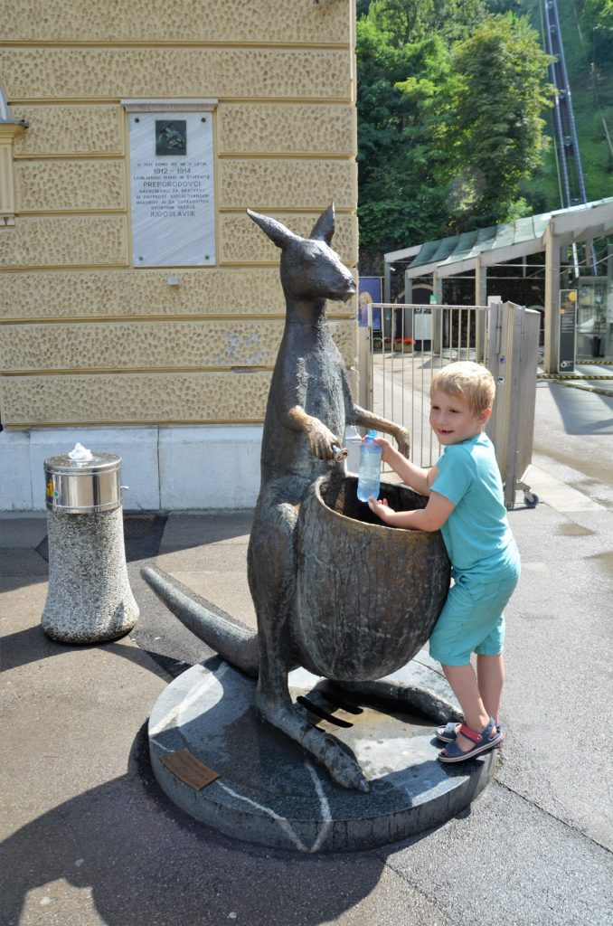 Yuri standing at a cangeroe, pouring water in a bottle. It was hot weather. Afternoon in Ljubljana.