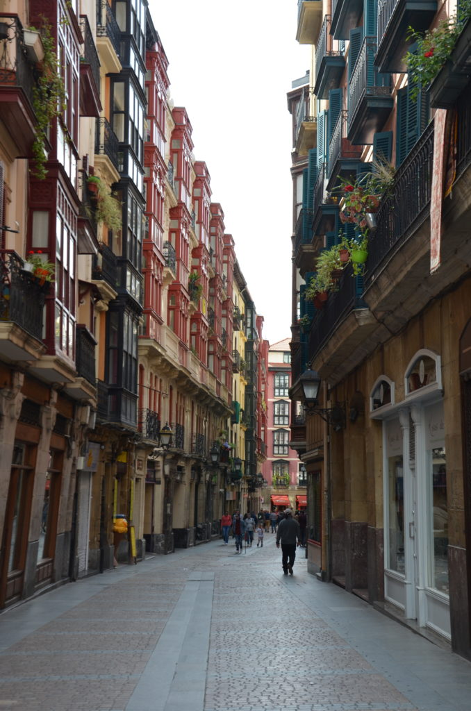 To show a picture from our 2019 travels. A small street with higher buildings, shops below, appartments above. The buildings have different colors and lots of plants.