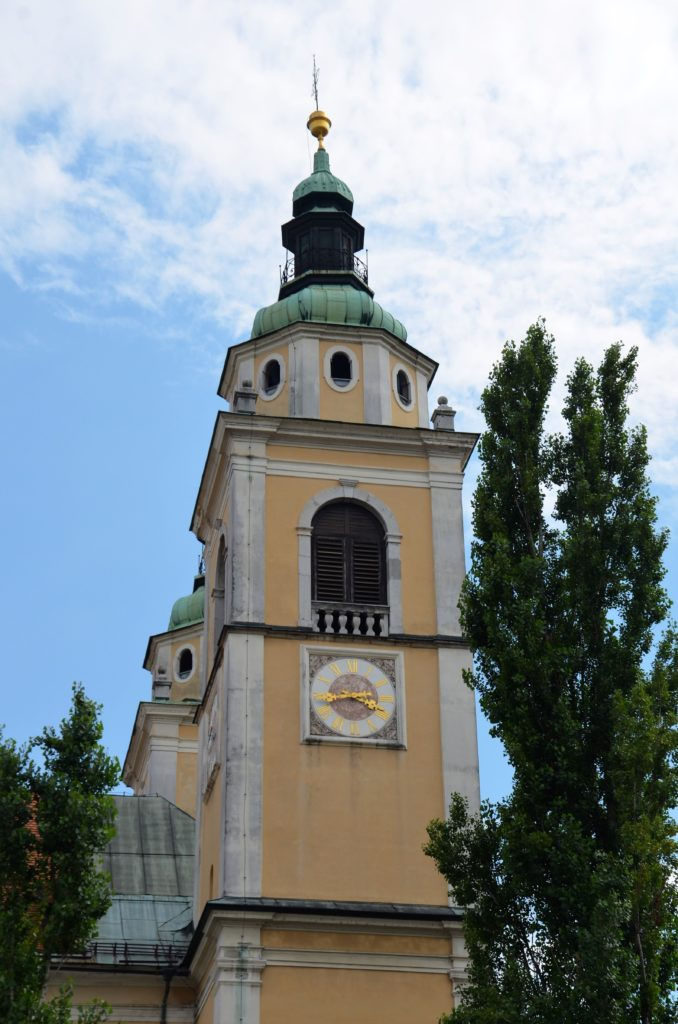 The upper part of a bell tower. A clock is on the tower. A tree to the right and a small one on the left. Blue sky with white clouds above and beyond. The tower is yellow plastered.