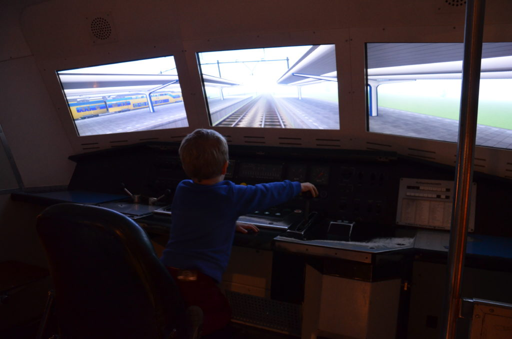 Yuri driving atrain inside the Spoorwegmuseum. he's sitting on a chair with panels in front of him. Through 3 windows a movie is playing from a trainstation. Part of Utrecht with kids.