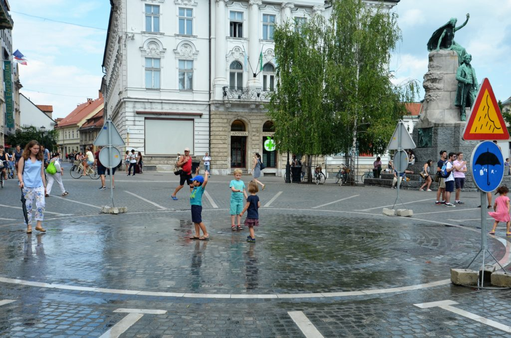 Yuri and some other kids are standing on a square. Only the square is wet. They let it rain there for the heat, to cool down.