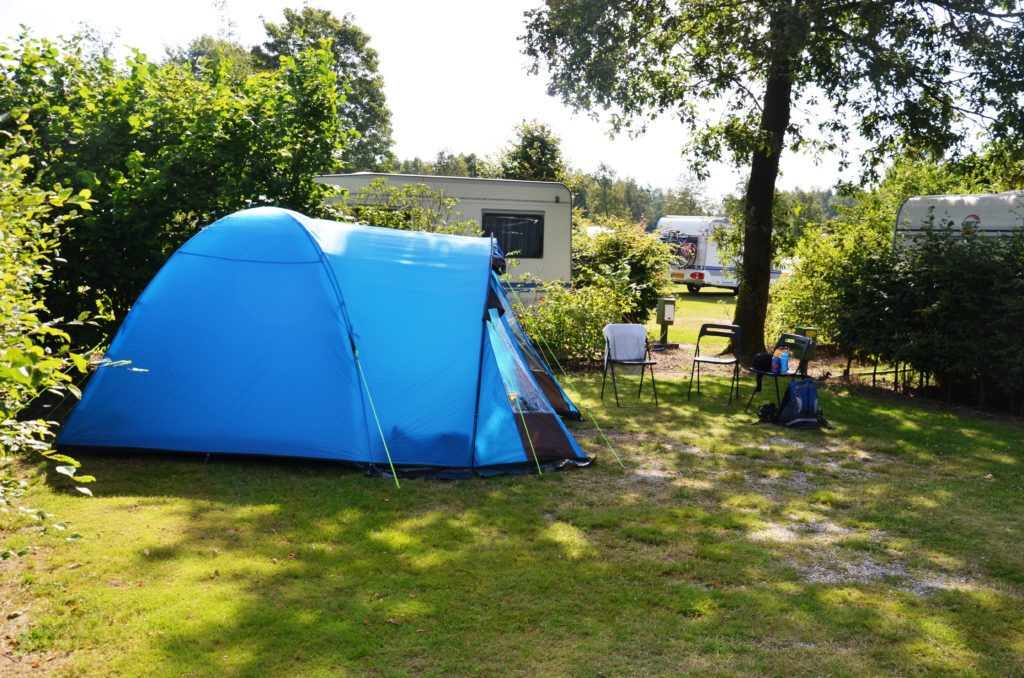 To show the size of the spots to camp on. A shaded grass place with trees marking off the boundaries. Our blue tent on it and chairs on the side. Campsites in The Netherlands.