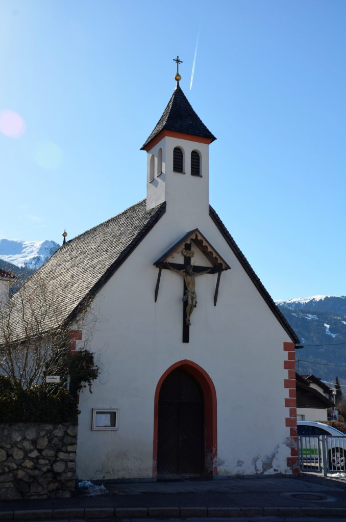 A small chapel, seen from the front. White plastered with a small tower in the front. Black tiled roof. A wooden Jesus figure on the front. Bushes on the side, mountains in the back and blue clear sky. This is one of the things to see on winter walks in Götzens.