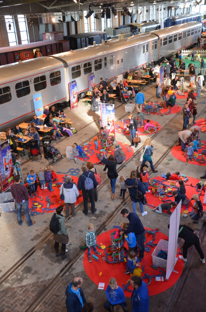 A hall filled with red blankets with Chugginton trainsets on them. People standing around them and kids playing on the rugs.