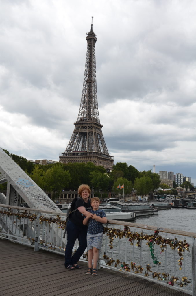 To show a picture from one our 2019 travels. In the back the Eiffle tower. Trees in front of it. Then the river Seine. Cosette and Yuri standing on a bridge with a lot of locks attached to it.