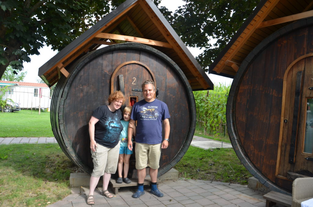 The 3 of us in the middle in front of a large wine barrel. Where we spend 2 nights in. Cosette on the left, Yuri in the middle, Paul on the right. On the right another wine barrel. Under and beneath green grass. Trees behind the barrels.