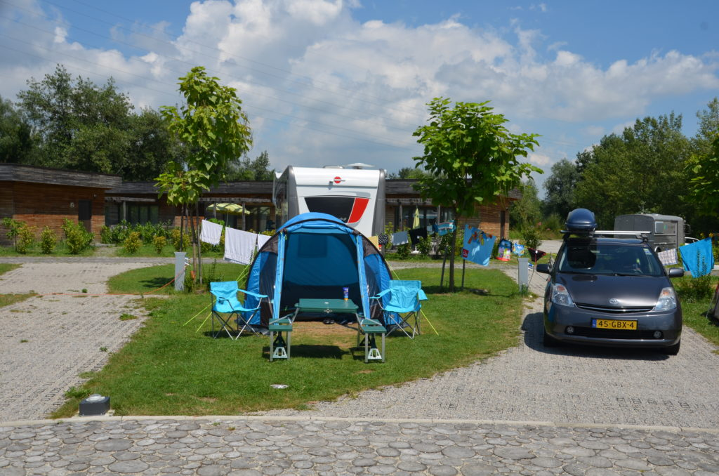 Our blue tent pitched on a grass field, for us alone, with next to the grass a paved place where our car is standing. Behind us another one of those spots. Campsites in Croatia.