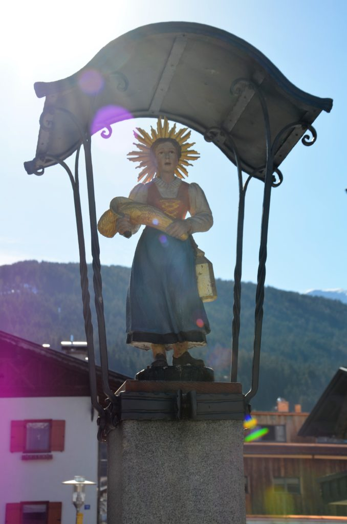 A Maria statue with a roof over it. Standing on a pedastale. With a blue skirt, white blouse, yellow shirt over it and a ray behind here head.