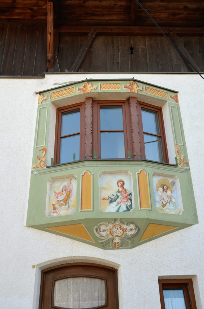 Beautifully colored alcove on a white plastered wall. The alcove is colored green, with wooden window stills. There are 3 painted pictures under the window. Visible on the winter walks in Götzens.