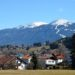 The town of Gotzens, Austria, with a grass filed in front and behind snowcapped mountains and clear blue sky. A view visible on the winter walks in Götzens.