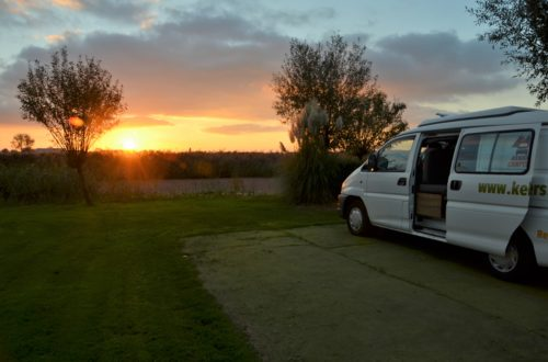 To show the magnificient sunset we had. n the right half of a white campervan. Standing on fake grass. The fake grass is surrounded by real grass. Behind the grass is bushes and a creek. Behind the creek is a field. ON the horizon the sun is setting and the sky is colored yellow, red and blue. Van life.