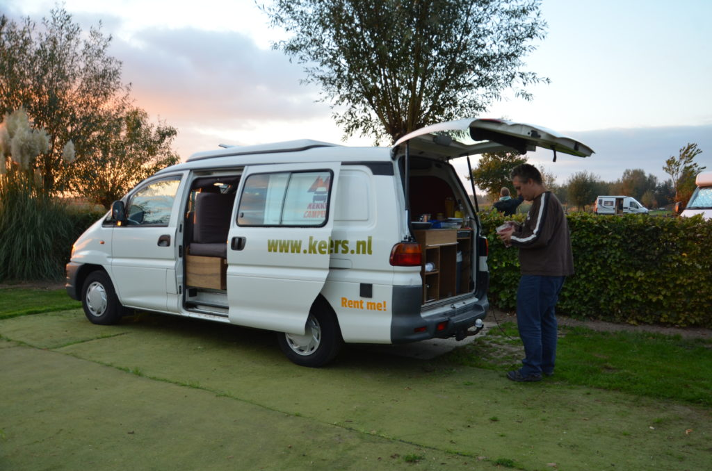 A white camper van, parked on fake grass, The side door is open. Behind is also open. Paul is standing their. Cooking our dinner on the kitchen in the camper van. Van life.