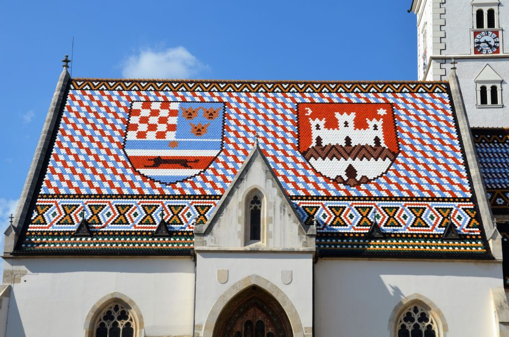 To show up close the colorful roof of the Saint-Marcus church. You see the roof of the nave of the church. Blue, red and white tiles. Two coats of arms.