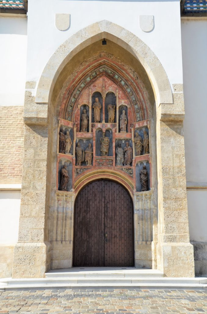 To show how beautifully decorated the Saint-Marcus church is. You see a wooden door, with carved out figures above it.