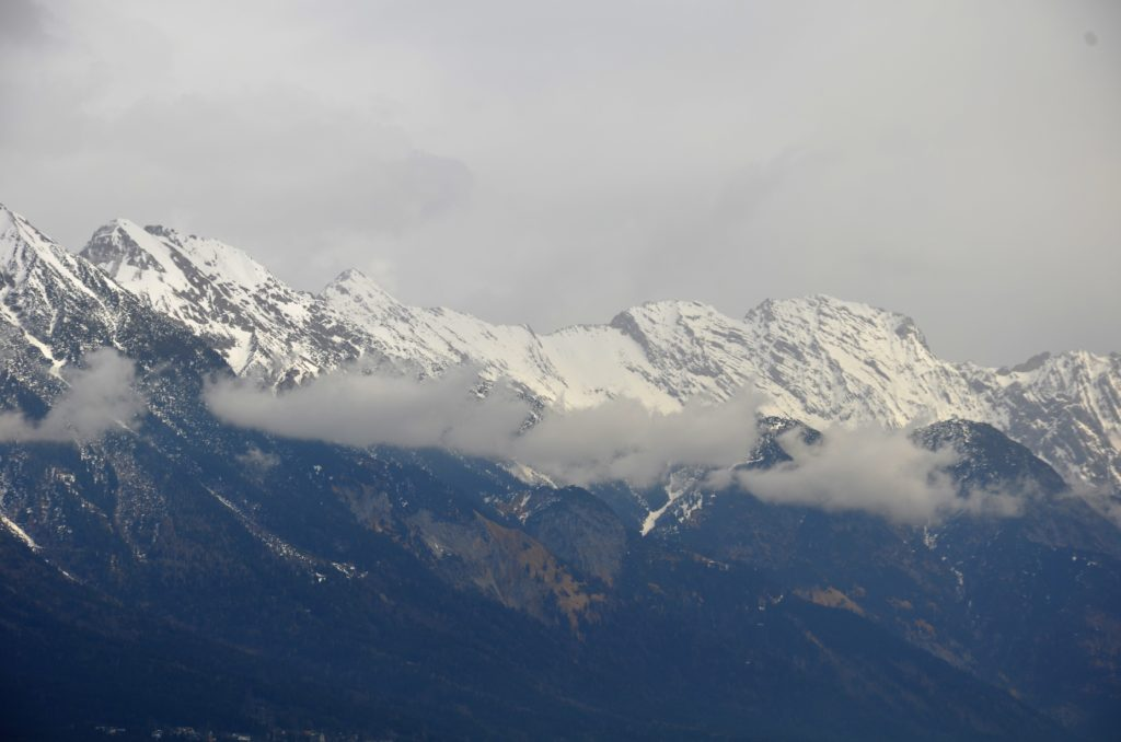 Snow capped mountains, the mountains are dark colored and covered in trees at the beginning, then there are low hanging clouds, above those clouds are the snow capped peaks. Above the peaks is an overcast sky. Views from winter walks in Götzens.