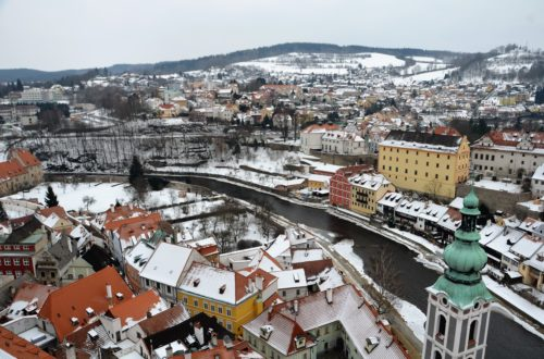 To show a picture of our 2018 travels. An overview of Cesky Krumlov, a river flowing through in the middle. The roofs and streets covered in snow.