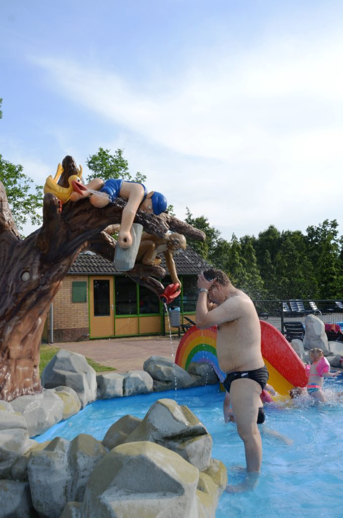 To show the kiddie pool on the campsite. A small, shallow kiddie pool outside. Fake stones surrounding it. A small slide in the back. Paul is standing under 'a shower'> The shower comes from a fake tree.