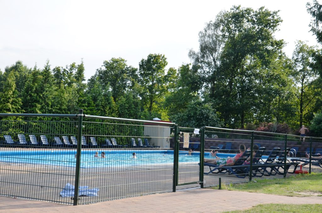 To show the swimming pool at the campsite, outside and surrounded by a high fence. A simple swimming pool, square formed, with a green fence around it. People swimming in it. Chairs on the sides. Campsites in The Netherlands.