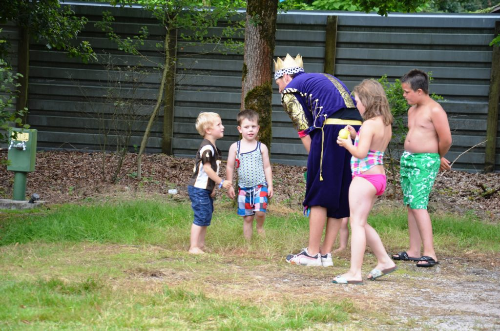To show something they do with the kids on the campsite. On a grass field Yuri is asking something at someone dressed up as a king. Other kids are standing around them. Campsites in the Netherlands