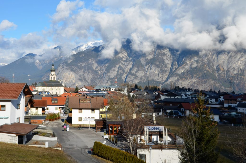 The town of Götzens in the forefront behind mountains the peaks covered in clouds. Part of the view on the winter walks in Götzens.