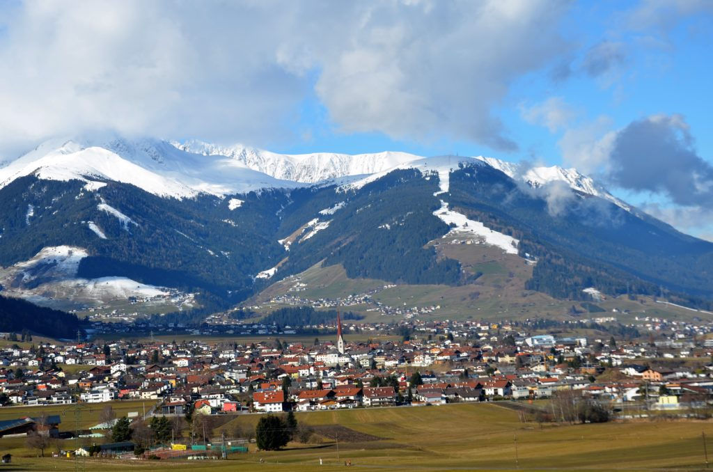 The town of Gotzens with mountains behind it and snow capped mountains. Clouded skies and a green grass field in front of the town.