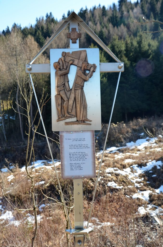 A station of the cross. Wooden figures, Jesus carying his cross on a stale statue, with text beneath it.