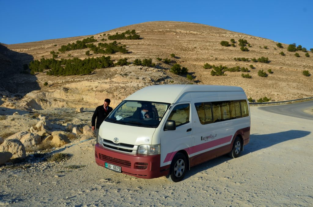 To show the van we traveled in, in our tour through Jordan. A white van with some red stripes. Standing still on the side of the road. Behind a mountain (rock) with some bushes. The chauffeur is standing next to the bus.