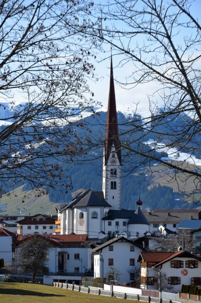 In the middle a church with alarge tower with a red roof. The church is white plastered and has blue tiles roofs. Trees in front, mountains in the back and the sky visible above. Houses surrounding the church