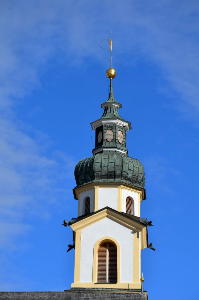 A church tower, the top of it against a blue clear sky