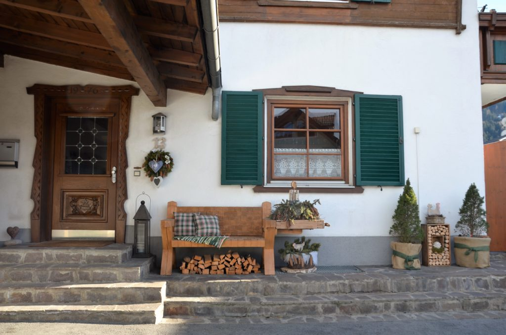 The front of a house with a bench in the middle, stairs in front, White plastered wall and a wooden door and window, green latches. The house is visible on the winter walks in Götzens.