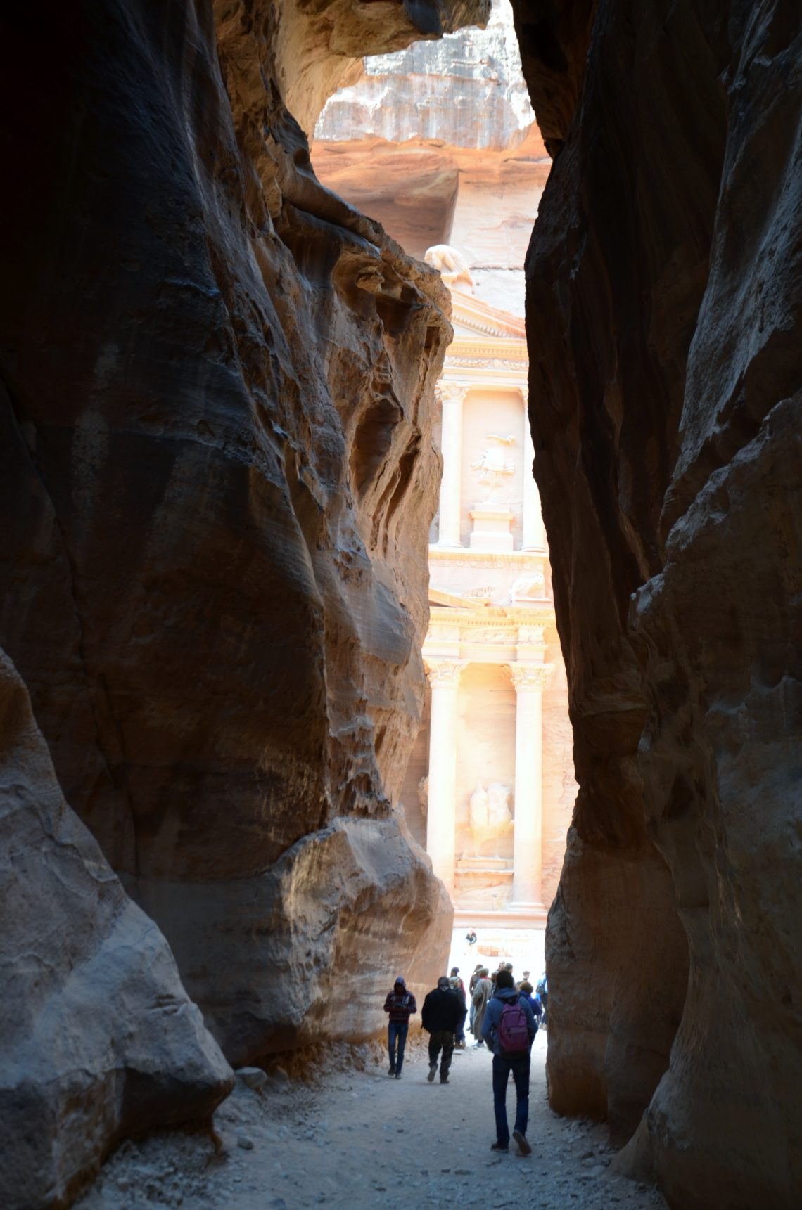 To show the first glimpses of the Treasury. A small canyon, rocks rising high. In front through the opening part of a building. In front lots of people walking. Tour through Jordan.