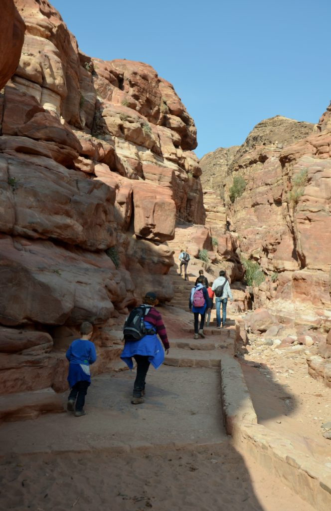 A picture to show there's a lot of walking and stairs in visiting Petra. A path with stairs in between the rocks. People walking up on them. The sun is shinning, clear blue sky.