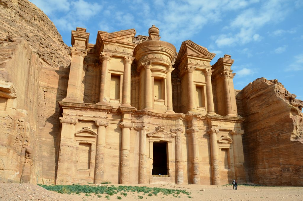 To show how beautiful the Monastry is in Petra. You see a large grave tomb carved out in the rocks. More yellowish here in the picture. In front a large almost empty square from yellow sand and a bit of grass.